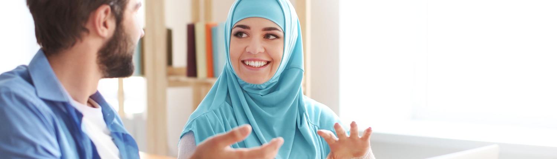 Junger Mann und Frau mit Kopftuch lernen gemeinsam