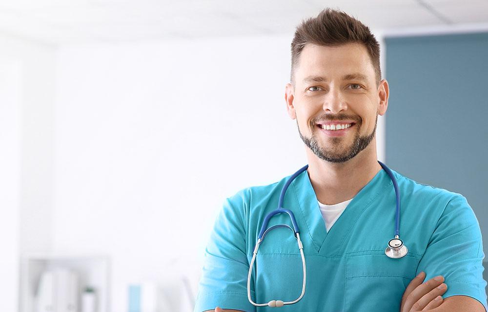 Junge männliche Pflegefachkraft in Klinik mit Stethoskop
