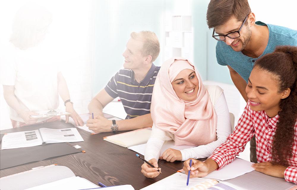 Schüler sitzen am Tisch und lernen Deutsch zur Sprachförderung
