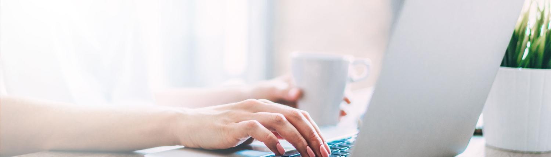 Frau sitzt an Laptop und hält Tasse in der Hand
