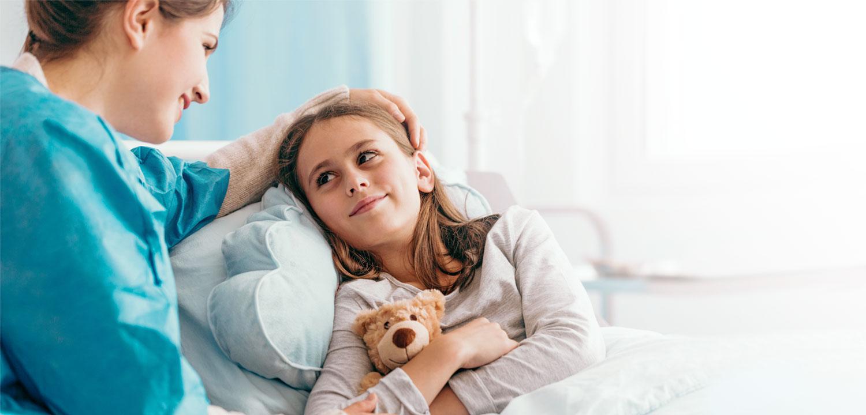 Lächelnde Pflegerin streichelt kleines, krankes Mädchen über den Kopf